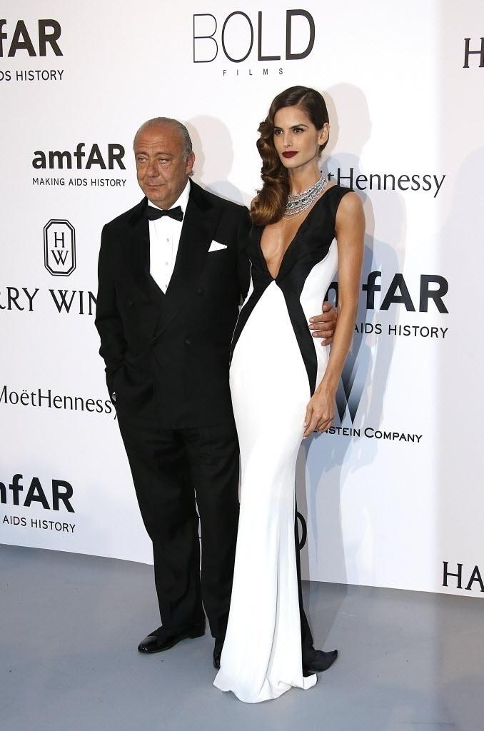 21.mai.2015 - O presidente, proprietário e fundador da Grisogono, Fawaz Gruosi, posa com a modelo brasileira Izabel Goulart na entrada do baile anual da amfAR realizado durante o 68º Festival de Cannes, na França