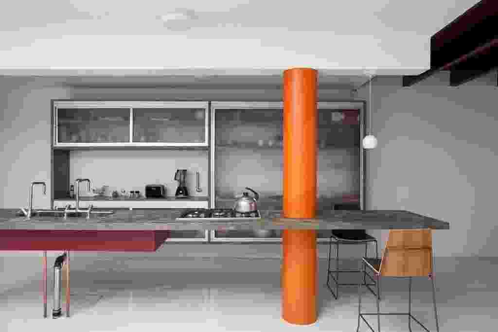 Casa térrea de 160 m² tem projeto de Guilherme Mendes da Rocha: detalhe da cozinha, cuja bancada de concreto contrasta com o pilar pintado de laranja. No piso, concreto desempenado com pintura epóxi branca - Fran Parente/ UOL