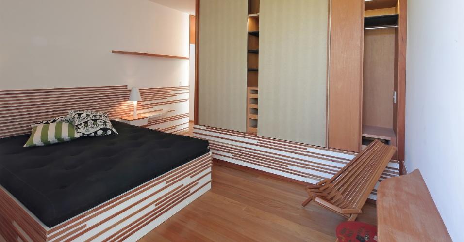 Cama, cabeceira e guarda-roupa seguem o mesmo padrão da marcenaria (Roma Móveis), com laminado melamínico branco e apliques de acabamento em madeira tauari.