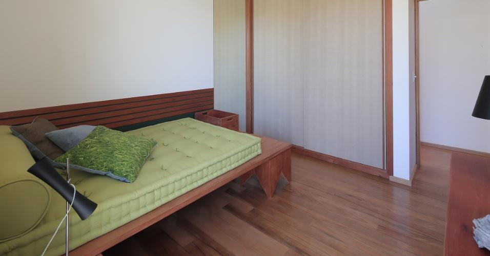Nos dormitórios, o piso é de tábuas de madeira cumaru, em tons próximos ao do acabamento de madeira tauari utilizado na marcenaria. A tela-mosquiteiro, aplicada às portas do armário, possibilitam a ventilação das roupas e objetos guardados. Para dar leveza ao cômodo, futons substituem os colchões sobre boxes ou camas (foto), que são como 'mesas de apoio'. Quase todos os móveis da casa Madrid, em Marília (SP), foram desenhados pela arquiteta Monica Drucker