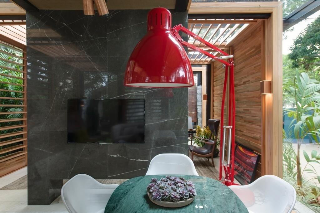 Casa Cor SP 2015 - Na área de jantar da Casa do Bosque, David Bastos optou pela imponente luminária de piso, na cor vermelha, direcionada sobre a mesa. No ambiente, as peças são da Casual Interiores