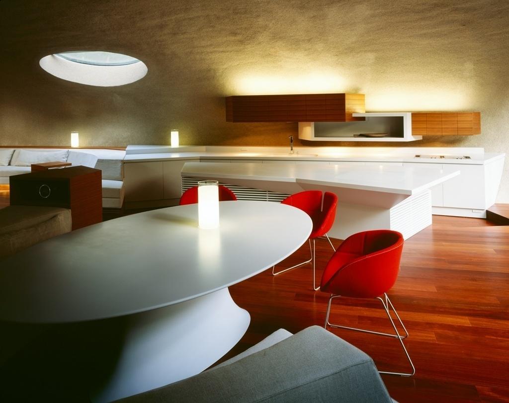 Na cozinha, o branco da marcenaria laqueada predomina e só é quebrado pelas cadeiras vermelhas. Os eletrodomésticos (AEG e Gaggenau) ficam todos embutidos nas bancadas e