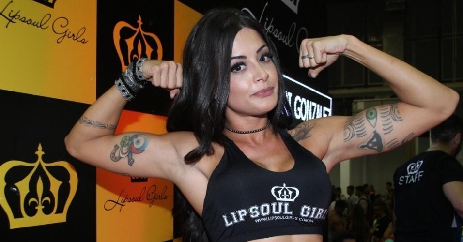 30.mai.2015 - Aline Riscado, bailarina do Faustão e garota propaganda de uma marca de cerveja, exibe músculos em feira fitness no Rio de Janeiro