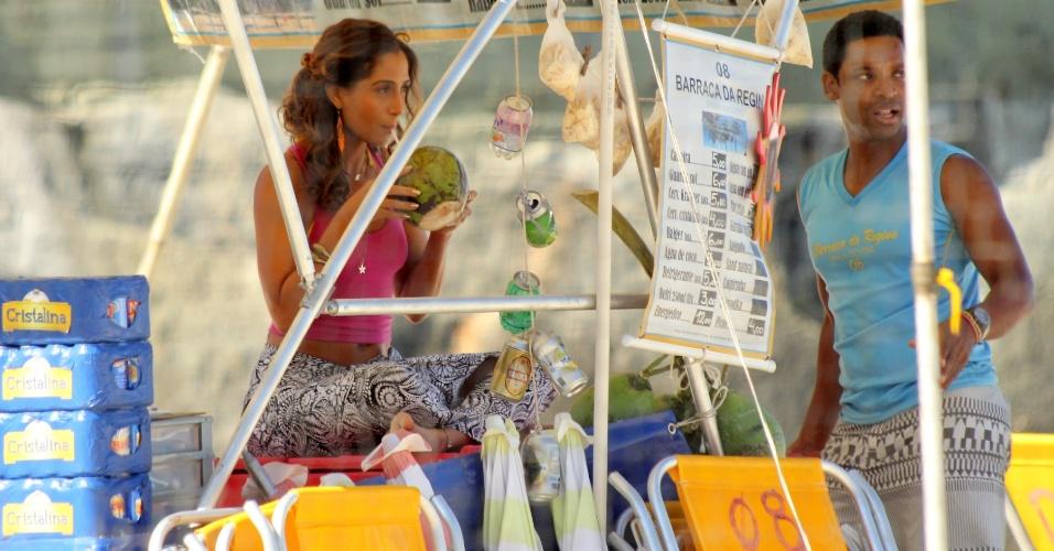 """3.jun.2015 - Camila Pitanga toma água de coco enquanto espera para gravar cenas de """"Babilônia"""" na praia do Leme, no Rio"""
