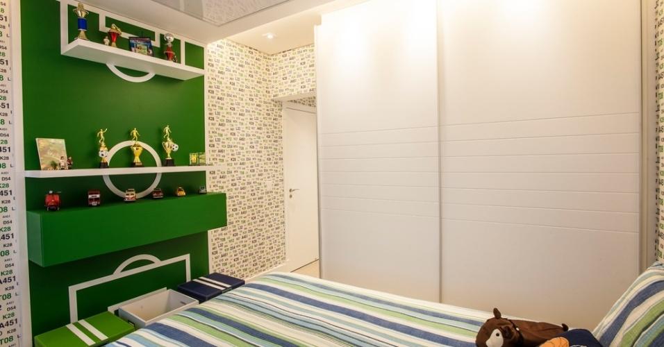 Deste ângulo, o quarto idealizado por Adriana Di Garcia revela-se lúdico, pois conta com um painel em marcenaria que segue o desenho de um campo de futebol. Ali, prateleiras e nichos organizam os troféus do jovem jogador