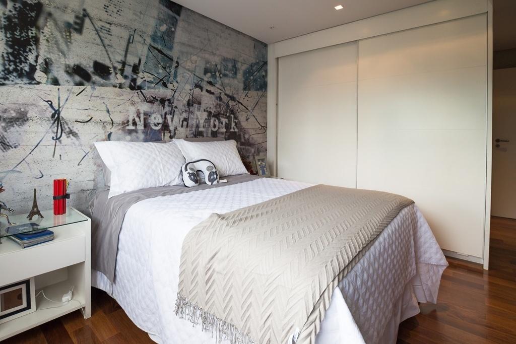 O papel de parede tipo grafite faz referência à cidade de Nova York e imprime o tom urbano ao dormitório do menino de 12 anos que ama tecnologia. Com 14,2 m², o espaço idealizado pela arquiteta Raquel Kabbani recebeu uma confortável cama e armários com portas de correr laqueadas