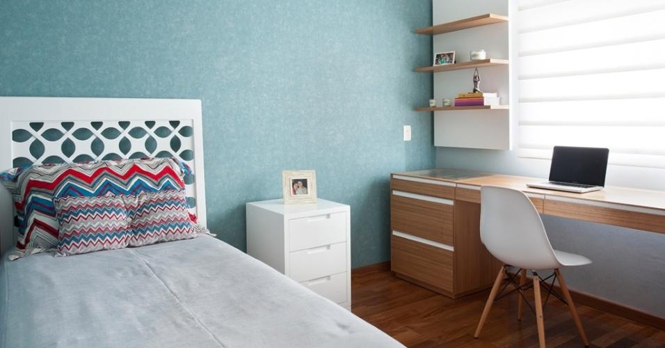 O dormitório com 9,55 m² foi pensado pela designer Adriana Fontana para a jovem moça, que precisava de espaço para os estudos e para guardar seus acessórios. Para dar aconchego, em uma das paredes foi aplicado o papel turquesa, que combina com a cama e o criado-mudo em MDF, brancos, da Casa Pronta. Na parede da janela está a ampla bancada, que aproveita a luz natural