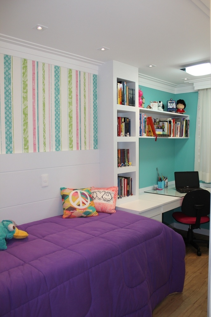 A arquiteta Pammela Resende Menezes desenvolveu este quarto com 8,5 m², para uma garota de 14 anos que precisava de espaço para livros e uma bancada grande de estudos. Entre a cama e a escrivaninha em L, foi planejada uma estante que é complementada pelas prateleiras apoiadas na parede. O papel de parede listrado destaca o painel de madeira pintado que delimita o espaço de dormir