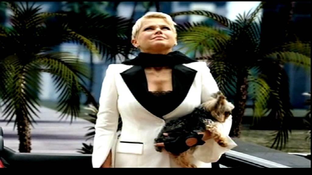 Xuxa chega aos estúdios da Record com Dudu, seu cachorro no colo