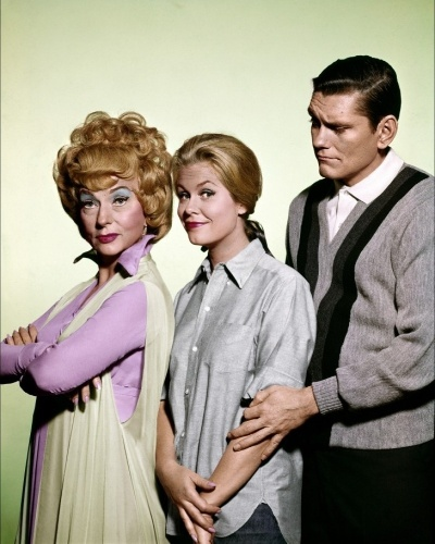 """""""A Feiticeira"""" (1964-1972): Os Stevens vivem felizes, não fosse o fato da mulher de James (Dick York/Dick Sargent) ser uma feiticeira. Samanta (Elizabeth Montgomery) pode fazer o que quiser com seus poderes, mas o trato entre ela e seu marido é que não faça uso deles. Só que as confusões que o casal se mete ? a maioria por causa da mãe dela, a bruxa Endora (Agnes Moorehead), que odeia James ?, sempre acabam se resolvendo com a ajudinha do nariz de Samanta, que resolve tudo com um mexidinha"""