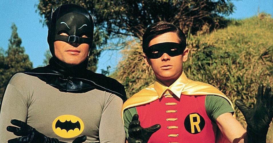 """""""Batman"""" (1966-1968): Nada do sombrio Cavaleiro das Trevas. O Homem Morcego ganhou uma série de televisão que emulava o espírito colorido e pop dos quadrinhos da década de 1960. Com Adam West (Batman) e Burt Ward (Robin), uma série de coadjuvantes (Batgirl, o mordomo Alfred, Tia Harriet, Comissário Gordon, Chefe O'Hara, Barbara Gordon), e seus vilões clássicos (Coringa, Pinguim, Mulher Gato, Charada, etc). Como esquecer do ZÓK! POW! CRASH!"""