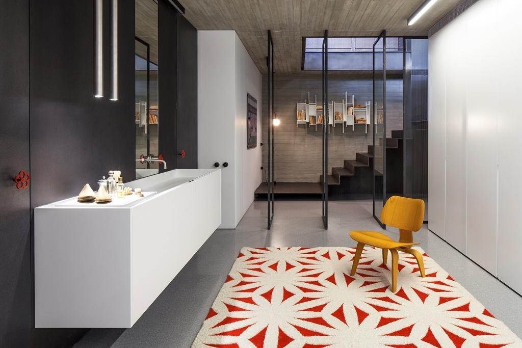 No piso subterrâneo está a suíte principal do apê em Tel Aviv, Israel. Nela está o amplo banheiro e um pequeno estar, que é o eixo de circulação que leva à cama. Atrás das portas de ferro (à esq. com puxadores vermelhos) estão os espaços para  banho e o vaso sanitário; enquanto as portas brancas (à dir.), também metálicas, dão acesso ao closet. O projeto de reforma é do escritório Pitsou Kedem Architects