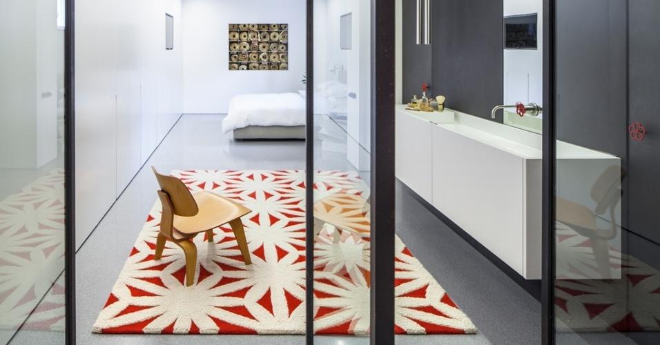 No piso subterrâneo está a suíte principal do apê em Tel Aviv, Israel. Um grande banheiro com um pequeno estar é o eixo de circulação que leva à cama (ao fundo). Atrás das portas de ferro (à dir.) estão os espaços para banho e o vaso sanitário. No projeto do escritório Pitsou Kedem Architects, toques de vermelho aquecem a ambientação e simbolizam a combinação entre a elegância clássica e a rusticidade do estilo industrial, composto de materiais crus