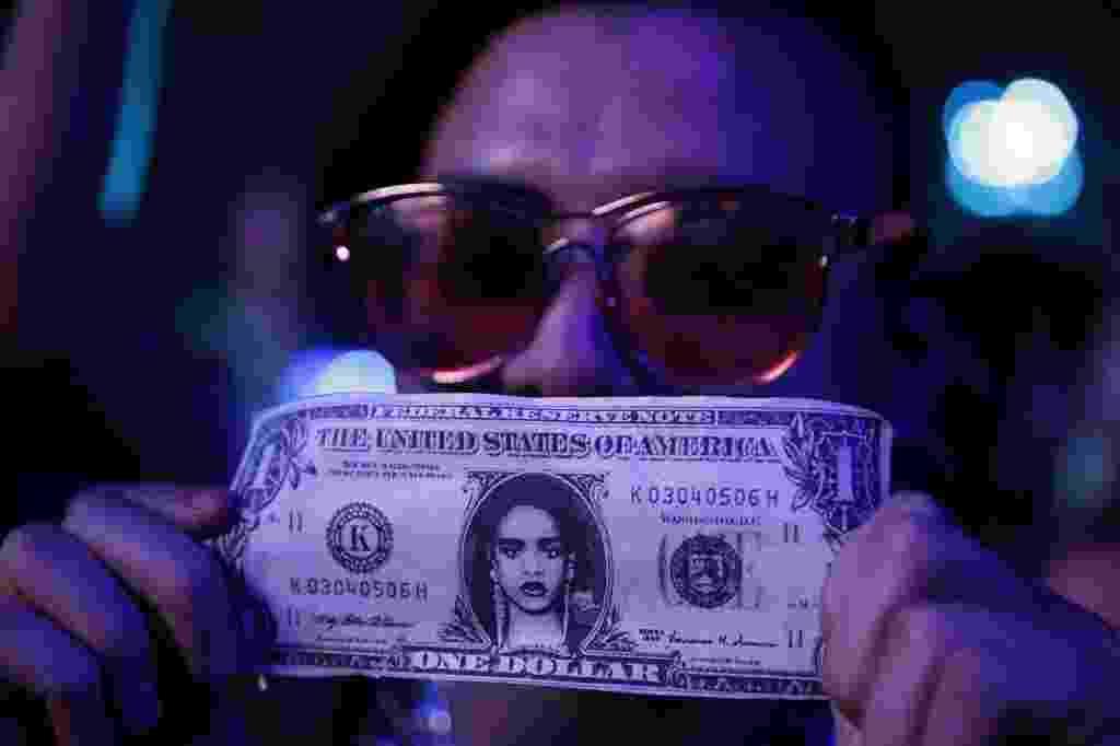 26.set.2015 - Fãs de Rihanna aguardam o início do show da cantora com notas de dólares com o rosto da diva pop - Marcelo Sayão/EFE