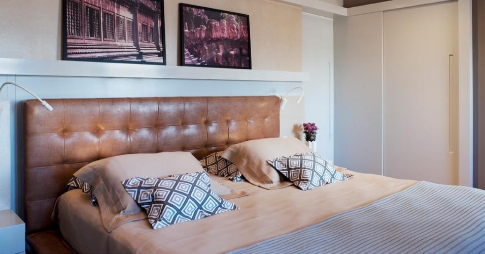 No quarto de casal, os lambris de madeira, a cabeceira estofada em couro, a parede pintada de marrom e a iluminação indireta aquecem o espaço. O projeto é do escritório KTA