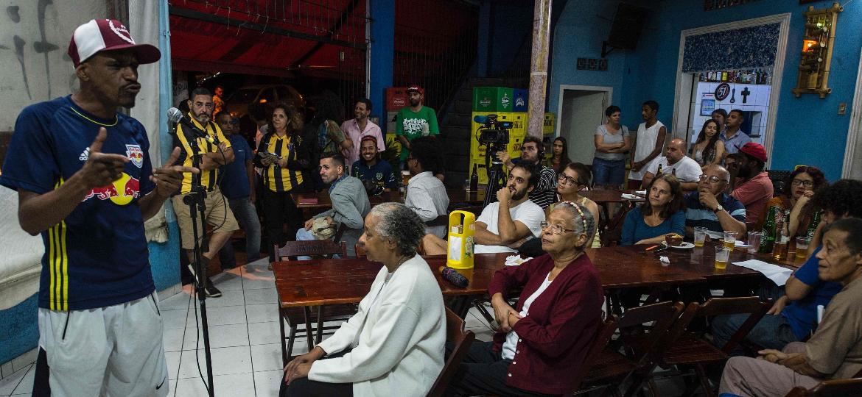 Integrantes da Cooperifa recitam poemas durante sarau em um bar no Capão Redondo - Nelson Almeida/AFP