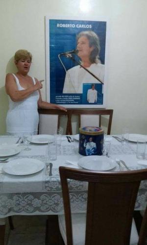 Simone posa ao lado da mesa de jantar que preparou em comemoração ao aniversário de 75 anos do músico completados em abril de 2016