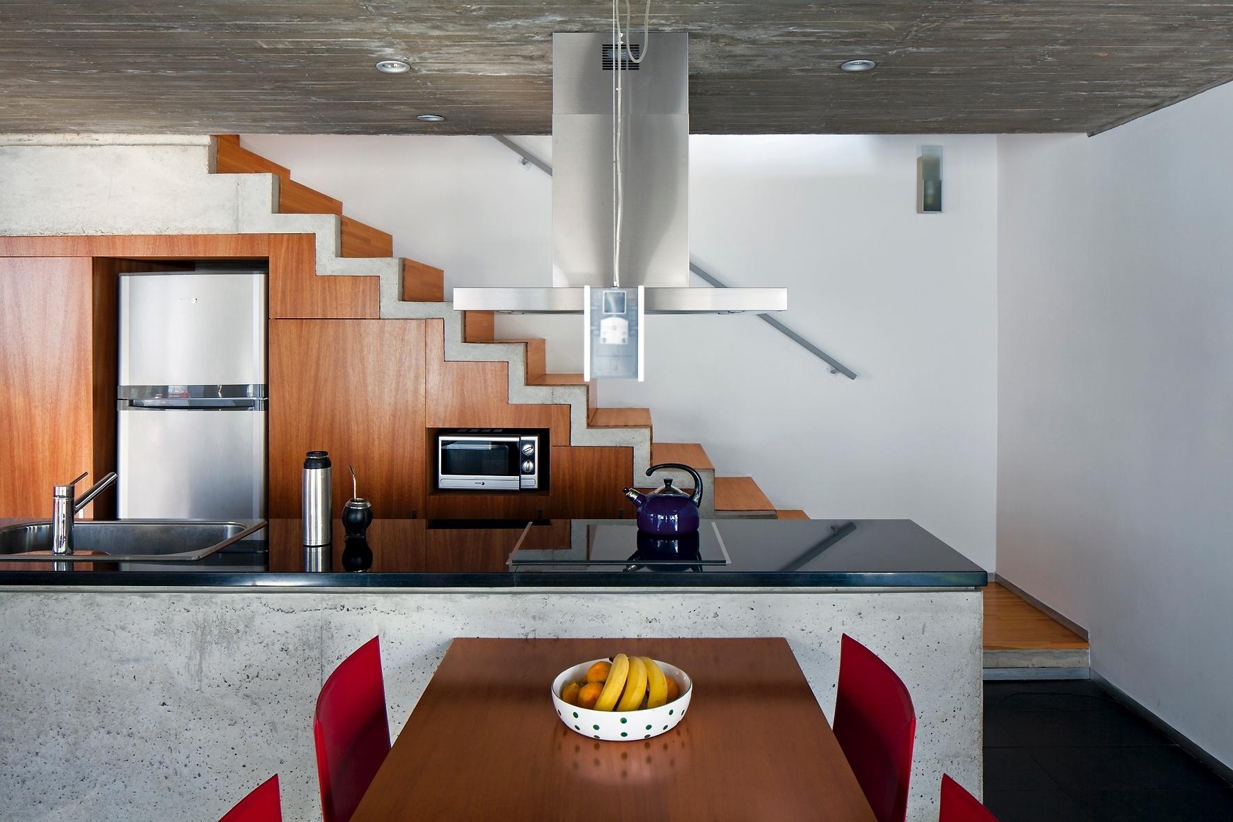 O fundo da construção concentra a circulação (escadas) para o pavimento superior e