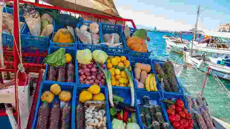 Vegetais em uma tenda do mercado em um barco no porto de Egina - Getty Images
