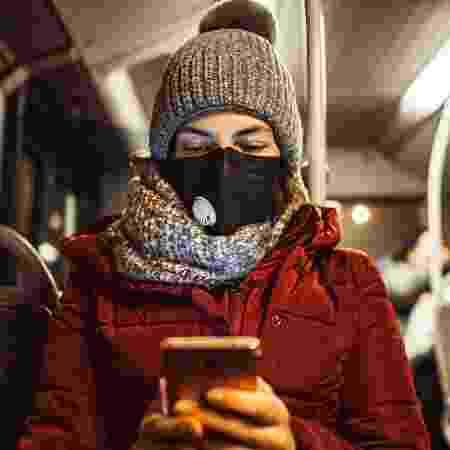 mulher lendo celular no ônibus, máscara, coronavírus, fake news - iStock