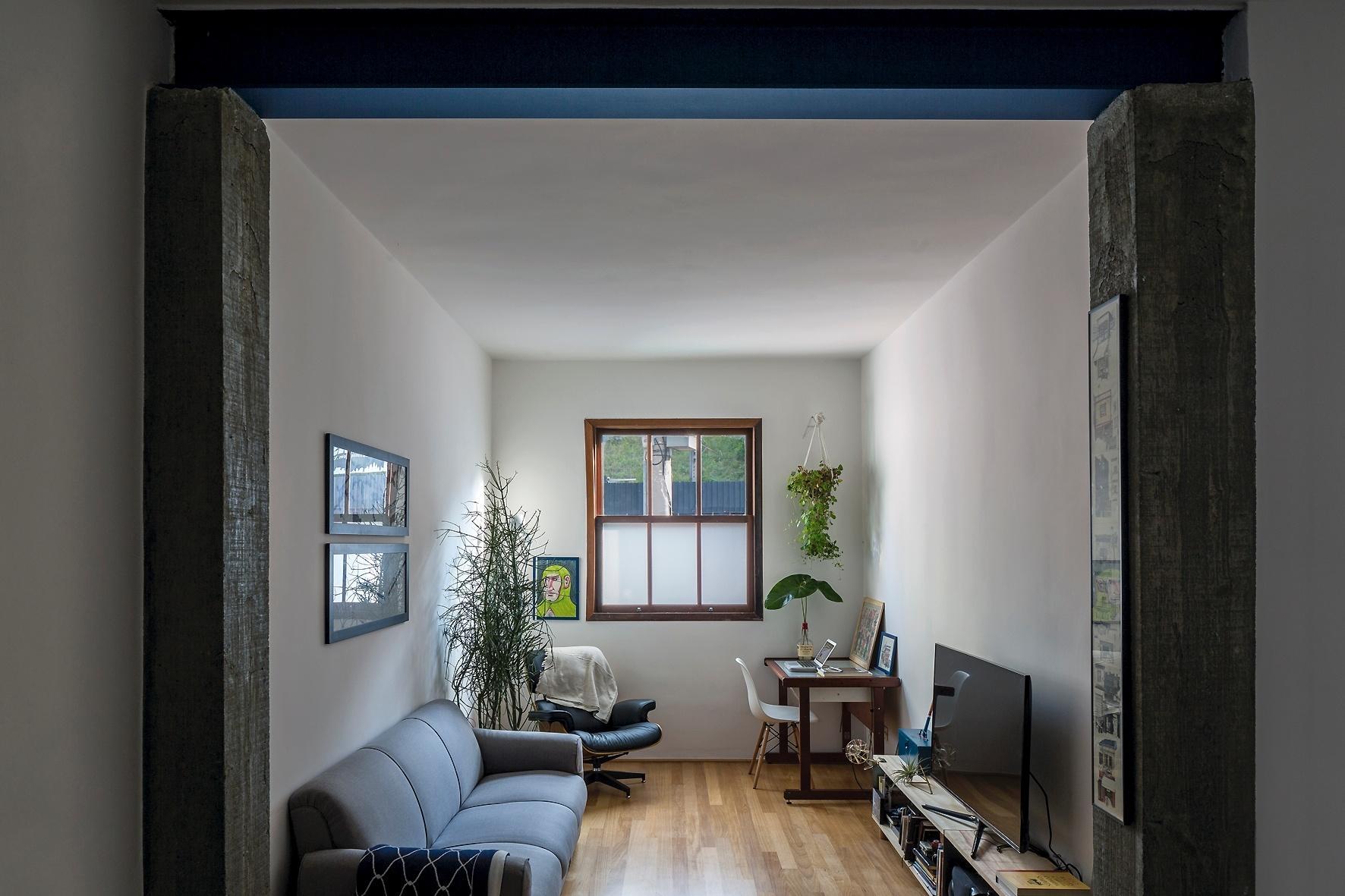 Voltado para a rua, o estar principal tem ambientação singela, com móveis em cores neutras e sóbrias: à esquerda, o destaque é uma poltrona desenhada por Charles e Ray Eames. Os pilares em concreto aparente emolduram o espaço, com reforma capitaneada pelo escritório Vapor 324
