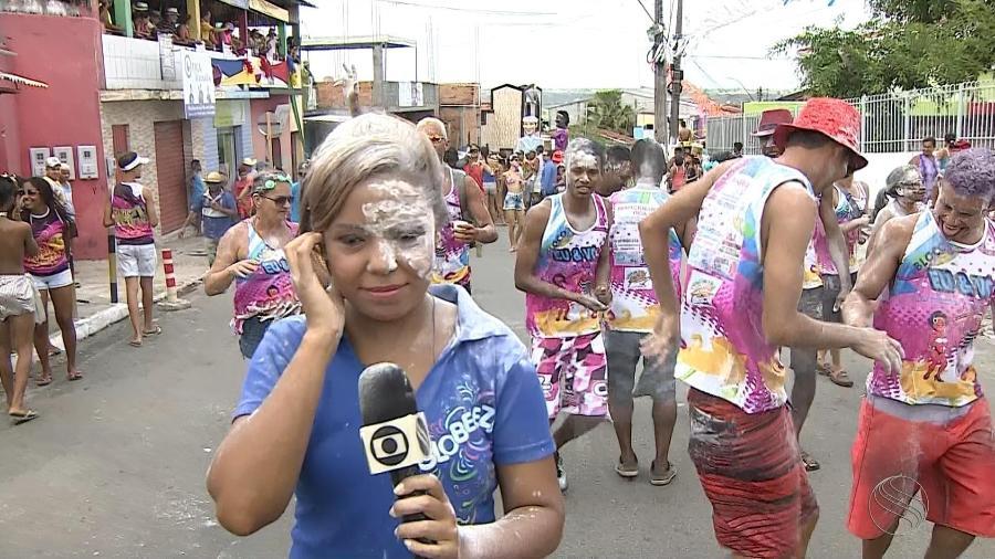A repórter Denise Gomes, da TV Sergipe, afiliada da Globo, leva banho de farinha durante festa de Carnaval - Reprodução/TV Globo