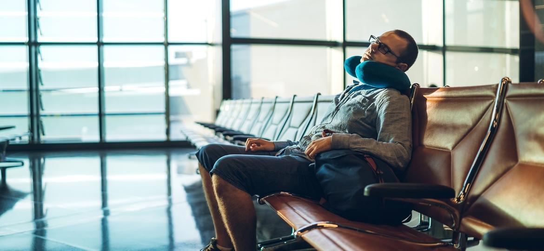 Viajante com travesseiro no pescoço no aeroporto - Getty Images