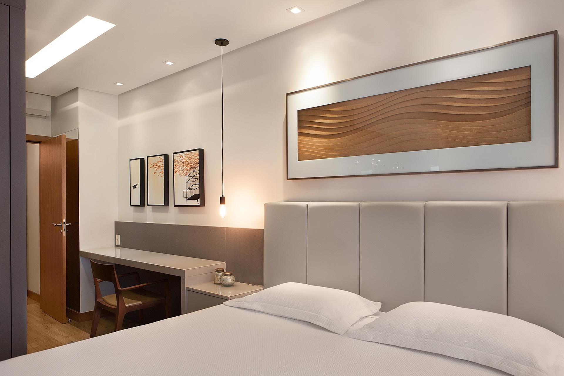 A suíte do casal do Apartamento em Floripa (SC) também foi resolvida com marcenaria. Em tom de cinza e laqueada, integra cama com cabeceira estofada, criado-mudo e escrivaninha. Aqui, o projeto do Pimont Arquitetura recorreu ao forro para acoplar a iluminação