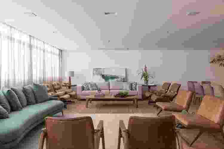 Neste projeto, o escritório utilizou na parede principal um sofá reto e de cor neutra que, por sua vez, alinhou-se com as quatro poltronas Charles Eames. No lado esquerdo, a profissional inseriu um sofá curvo com tecido tecnológico verde, usado para ver a TV localizada no painel à frente - Rafael Renzo - Rafael Renzo