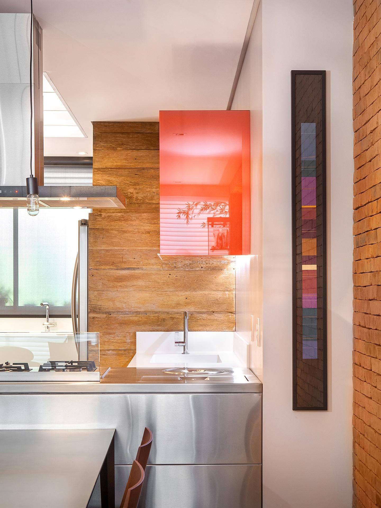 Detalhe da bancada da cozinha: em aço inox, abriga o cooktop e compartimentos para as lixeiras. Sobre ela, a coifa ajuda a renovar o ar, nos momentos de cocção. O armário é de vidro no tom coral. Sob ele, o tampo da pia em Corian branco se sobressai na parede de madeira de demolição. Apartamento em Floripa (SC), com interiores assinados do Pimont Arquitetura
