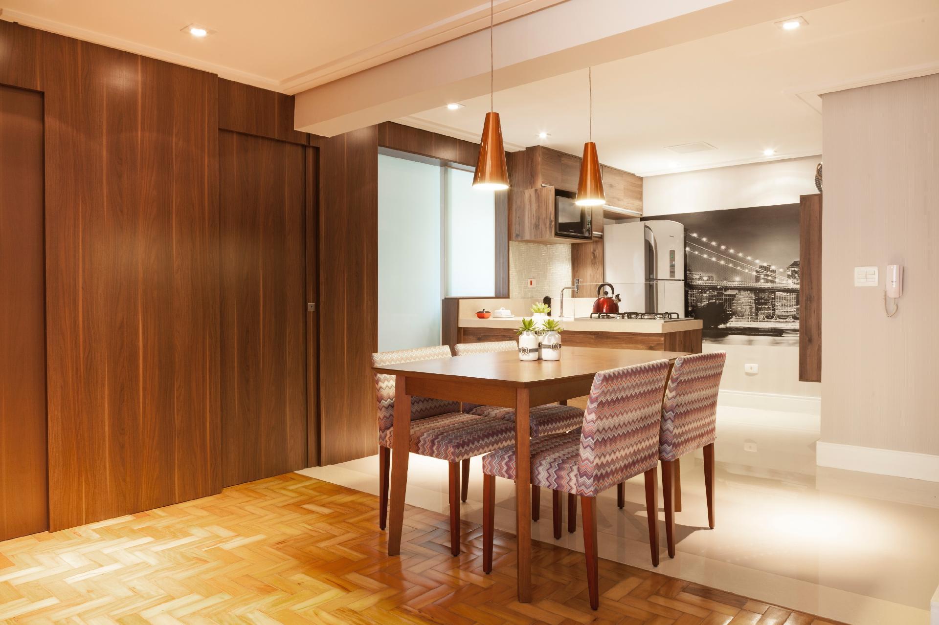 Com a reforma idealizada pelo escritório Biarari & Rodrigues, o jantar ficou posicionado entre a área 'gourmet' e o estar. A mesa de madeira faz jogo com as cadeiras forradas em tecido 'chevron'. Note que os pendentes acobreados são simétricos. Ao fundo, está a cozinha, agora aberta para o social e delimitada pelo balcão com base amadeirada, combinando com a proposta do design de interiores
