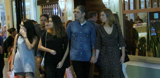 William Bonner e a namorada caminham de mãos dados pelo shopping. As filhas dos jornalistas acompanham o casal