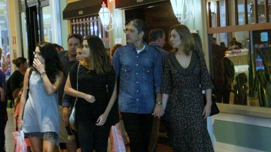William Bonner e a namorada caminham de mãos dados pelo shopping. As filhas dos jornalistas acompanham o casal - AgNews