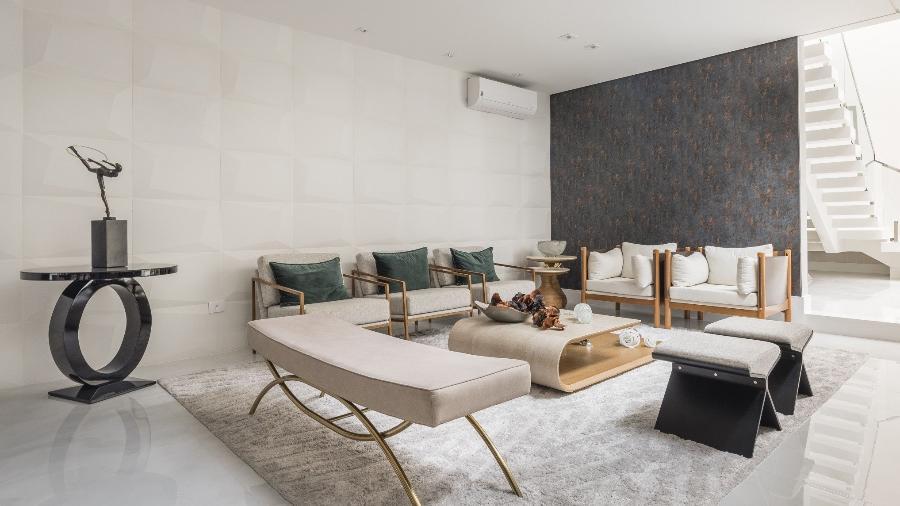 A sala de estar, em tons leves, ganha destaque com o papel de parede escuro, que também lembra aço corten em algumas partes. Papel de parede do tipo vinílico  - Henrique Ribeiro