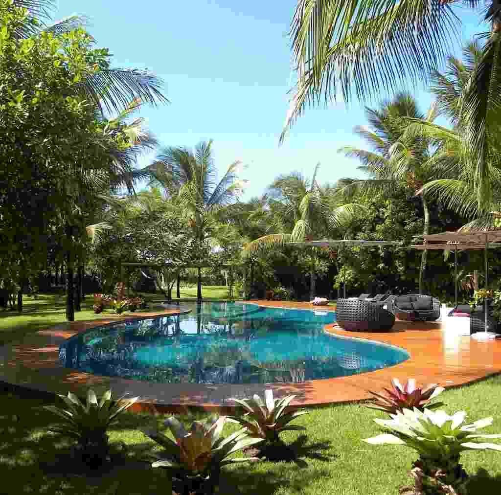 Junto ao deck da piscina com formato orgânico, o paisagista Marcelo Faisal dispôs coqueiros (Cocos nucifera L.) e bromélias. Para o relaxamento dos usuários, confortáveis móveis de fibra e ombrelones. O jardim com 11 mil m², de uma residência em Trancoso, na Bahia, é baseado em plantas regionais, características da restinga - Divulgação