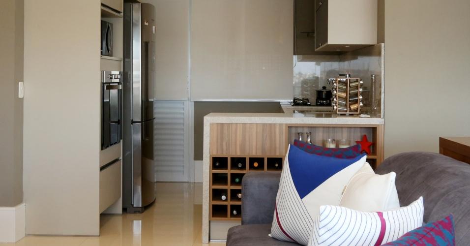 Para aproveitar melhor a reduzida metragem da cozinha, a arquiteta Débora Dalanezi previu armários planejados com eletrodomésticos embutidos. No ambiente integrado, nichos na lateral da bancada armazenam as garrafas de vinho e persianas (ao fundo) escondem a área de serviço