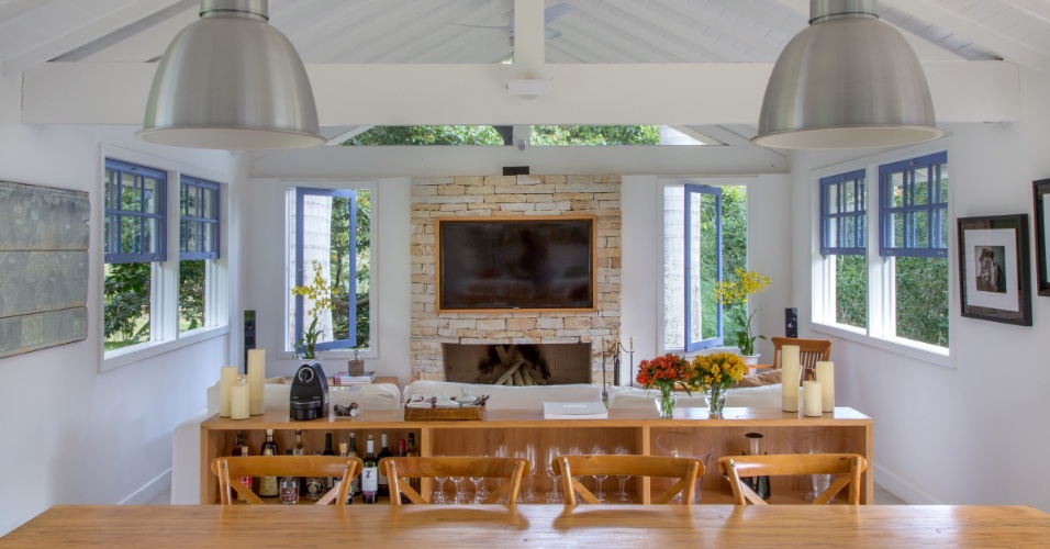Na outra extremidade do galpão que abriga o espaço de convívio do sítio Marigold, com projeto do arquiteto André Luque, está uma sala. O ambiente está interligado com a cozinha gourmet. No estar, lareira e home theater acolhem os visitantes, assim como a grande mesa para 12 convivas (em primeiro plano)