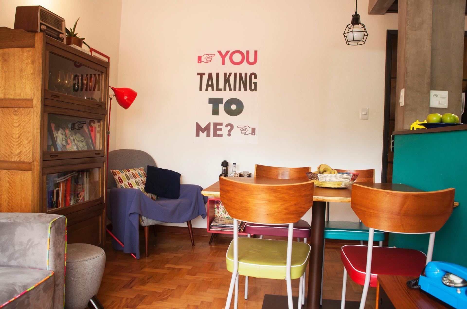 No canto de leitura, com luz focada própria (luminária vermelha de piso, da Tok&Stok), uma poltrona com pés-palito (Oppa) vem acompanhada pelo pufe redondinho em tom de cinza. Na parede, o adesivo divertido com cara de 'lambe-lambe' substitui os quadros. O apê na Aclimação, em São Paulo, foi reformado pelo escritório Dois Projetos