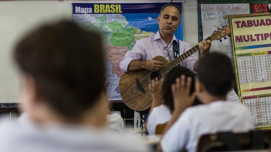 O professor Roberto de Oliveira Ferreira toca violão para entreter os alunos e desviar a atenção das crianças dos recorrentes tiroteios na zona oeste do Rio - Ricardo Borges/Folhapress