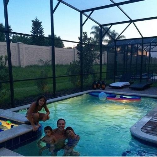 """11.jul.2015 - Rodrigo Faro se diverte com as filhas, Maria, Helena e Clara, em piscina em Orlando, na Flórida (Estados Unidos). """"E a bagunça continua aqui na casa de Orlando...Piscina às 10 da noite!!!!!Que delícia!!!!!"""", escreveu o apresentador em foto publicada por ele no Instagram"""