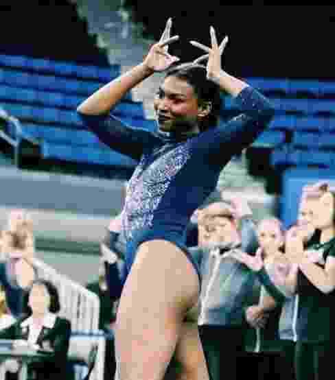 A ginasta americana Nia Dennis faz o gesto de por uma coroa na própria cabeça - undefined