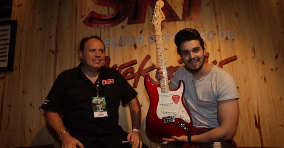 20.set.2015 - Luan Santana com o luthier John Cruz que fez uma guitarra para ele