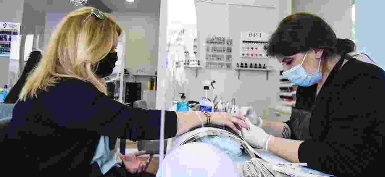 Em Atenas, um bloqueio transparente de acrílico separa manicure e cliente, que estende a mão por uma abertura na proteção - NurPhoto/NurPhoto via Getty Images