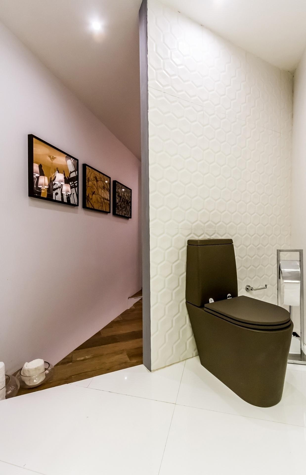 No segundo pavimento, o banheiro tem louça escura e parede revestida com cerâmica de grande formato e textura hexagonal. O ambiente faz parte do Refúgio Contemporâneo, projetado por Eduardo Baldelomar para a Casa Cor Bolívia