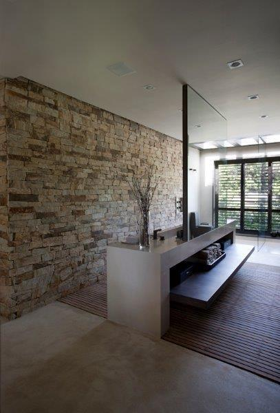 Com parede de pedras, o banheiro da suíte principal da casa Areia possui um deck de madeira onde fica o lavatório. Ao fundo, a arquiteta Debora Aguiar dispôs a área de banho