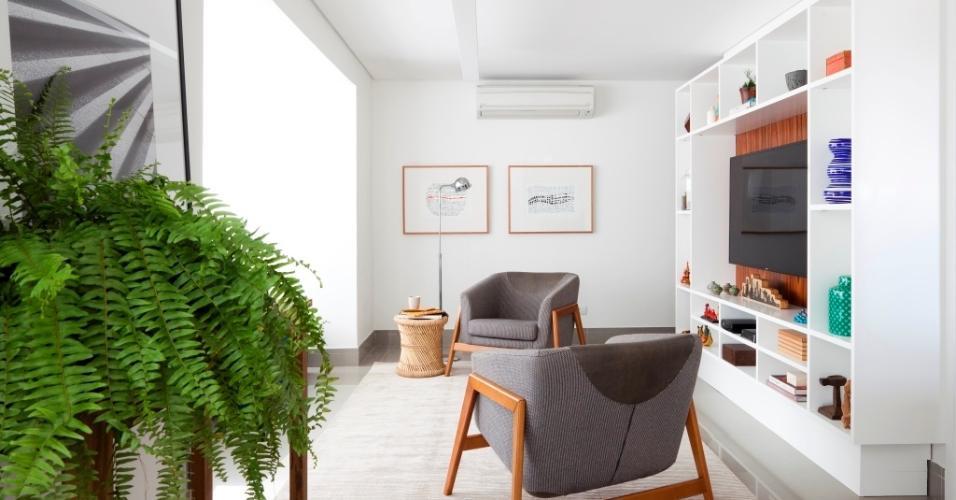Pontos sutis de madeira aquecem a sala do apartamento Alto do Ipiranga, onde predominam o branco e o cinza. Também são focos de cor viva as plantas de meia-sombra, com destaque para as samambaias. Viçosas, elas reforçam o toque natural no projeto de interiores do escritório Iná Arquitetura
