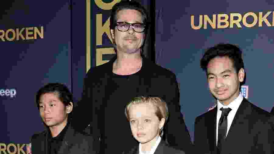 Brad Pitt com os filhos Pax, Shiloh e Maddox em estreia norte-americana da Universal Pictures em dezembro de 2014 - Robyn Beck/AFP