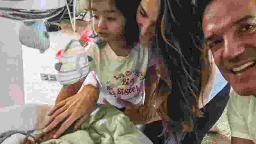 Carlos Machado, a mulher Ivy Rocha e a filha Luna observam o novo integrante da família, Luca - Reprodução/Instagram