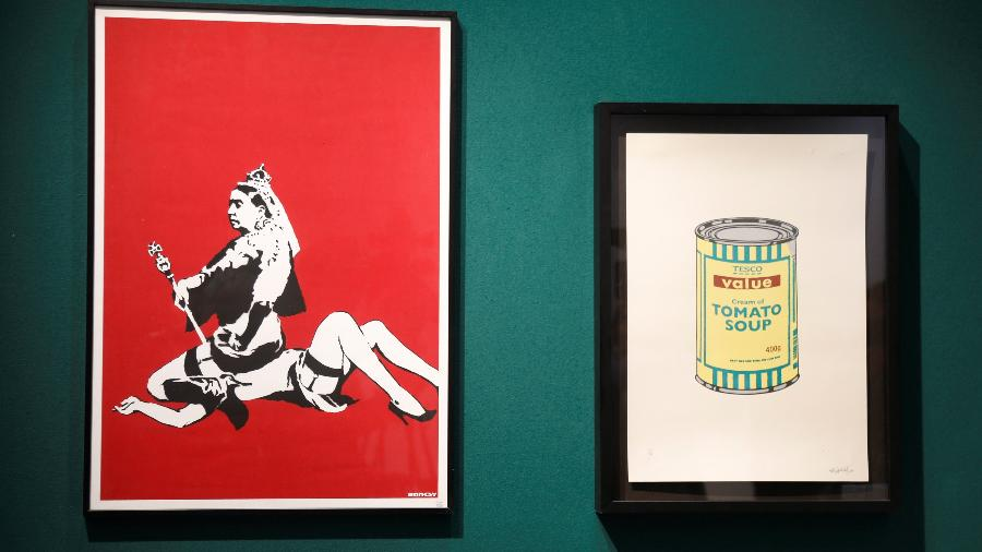 "As obras ""Queen Vic"" (2004) e ""Soup Can (Yellow/Emerald/Brown)"" (2005), de Banksy - Charles Platiau/Reuters"