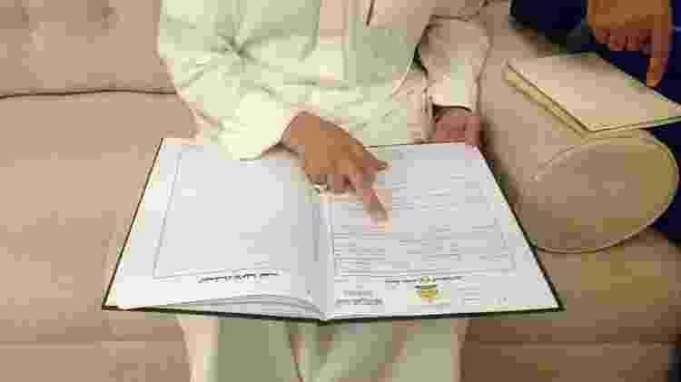 Clérigo Abdulmohsen al-Ajemi mostra exemplos de contratos de casamento - AFP